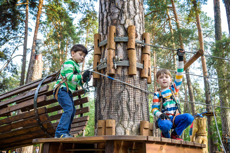 Two little boy boys kid in a helmet and with a safety carbine goes on a rope on the background of forest and sky. Healthy games outdoor.