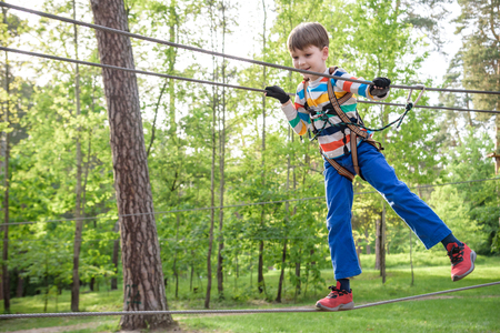 Cute child boy playing. Artworks depict games at eco resort which includes flying fox or spider net. Every childhood matters. Toddler age. Children fun. Stock Photo - 124702557