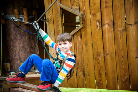 Boy climbing up into a treehouse. safety carbine goes on a rope on the background of forest and sky. Healthy games outdoor.