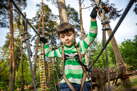 boy climbs in a high wire park above the ground. ziplining. boy on the zip line. kid passes the rope obstacle course. Foto de archivo - 124710136