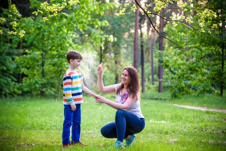 Young woman mother applying insect repellent to her son before forest hike beautiful summer day or evening. Protecting children from biting insects at summer. Active leisure with kids