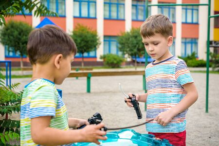 Two Boys playing with modern spin top outdoors. Entertainment game for children. Top, triggered by a trigger. Kids having a tournament on arena or battle field. Banco de Imagens