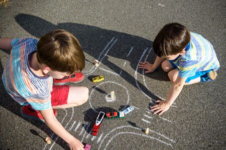 Two brothers sibling kid boy having fun with picture drawing traffic car with chalks. Creative leisure for children outdoors in summer. Difficult traffic rules education friendship concept. Imagens