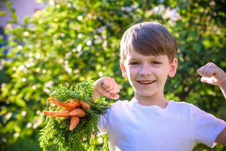 A boy in a light T-shirt celebrating a happy, smiling laugh with raising hands on a nature background, holds in his hand a bunch of carrots, copy space, close-up Фото со стока