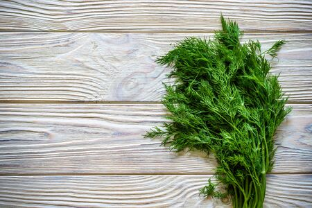 Bunch of dill isolated on a wooden background with space for text. Top view. Selective focus. Food for vegetarians.