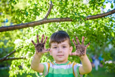 A young Caucasian boy showing off his dirty hands after playing in dirt and sand outdoors sunny spring or summer evening on blossom trees background. happy childhood friendship concept.