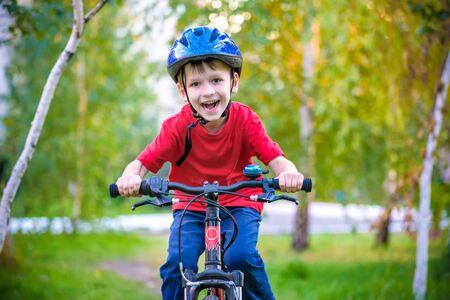 Ein kleiner weißer Kleinkindjunge in einem Schutzhelm auf dem Kopf sitzt auf einem Kinderfahrrad. Kleinkind auf einem zweirädrigen roten Fahrrad freut sich. Ein schlaues Lächeln auf dem Gesicht des Kindes.
