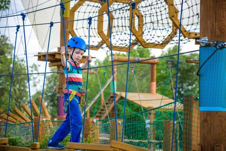 happy boy on the zip line. proud of his courage the child in the high wire park. HDR Stock Photo