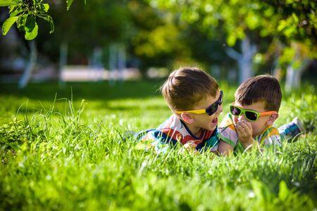 Glücklicher lächelnder Junge Geschwisterbruder, der sich auf dem Gras entspannt. Nahaufnahme mit Kopierraum. Vorschulkinder, die Sonnenbrillen-Sommerferienlager tragen. Entspannungsglück Kindheitsfreundschaftskonzept.