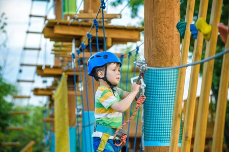 brave little boy having fun at adventure park and smiling to camera wearing helmet. toddler climbing in a rope playground structure. Scout practicing rappelling Stock Photo