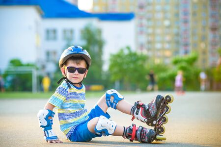 Happy boy in a protective helmet and protective pads for roller skating. Tired boy sitting and resting before start riding again. Active leisure summer holidays time for kids.