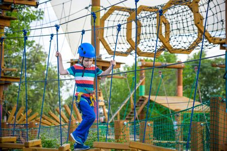 happy boy on the zip line. proud of his courage the child in the high wire park. HDR Stock Photo - 129887920