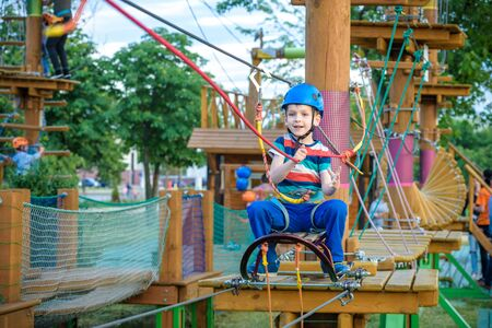 Little cute boy enjoying activity in a climbing adventure park on a summer sunny day. toddler climbing in a rope playground structure. Safe Climbing extreme sport with helmet and Carabiner. insurance Stock Photo