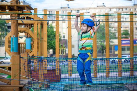 Little cute boy enjoying activity in a climbing adventure park on a summer sunny day. toddler climbing in a rope playground structure. Safe Climbing extreme sport with helmet and Carabiner. insurance Stock Photo - 129880384