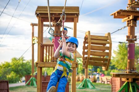 Little cute boy enjoying activity in a climbing adventure park on a summer sunny day. toddler climbing in a rope playground structure.