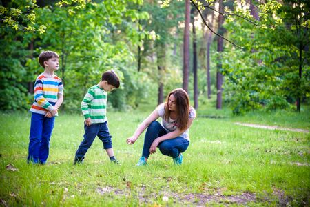 Young woman mother applying insect repellent to her two son before forest hike beautiful summer day or evening. Protecting children from biting insects at summer. Active leisure with kids. Zdjęcie Seryjne