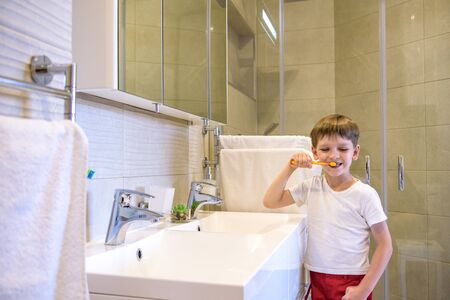 A cute little boy is brushing his teeth with a toothbrush. On a pure white T-shirt in which he is dressed you can make an advertising inscription. The concept of childrens health, medicine.