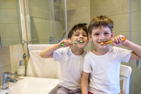 Closeup portrait of twins kids toddler boy brother in bathroom toilet washing face hands brushing teeth with toothbrush playing with water, lifestyle home style, everyday moments, morning routine 写真素材