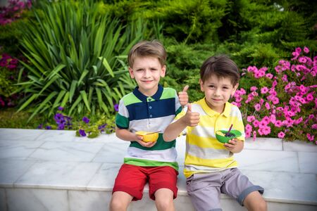 Tasty summer obsession concept. Happy young handsome hipster boys wearing colorful polo t-shirts, hugging, eating mini melts ice cream in heat cap over summer city park green nature plants background.