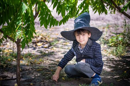 boy in pointed hat playing with magic wand outdoors. Little wizard. Halloween concept. Imagens