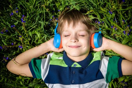 Smiling boy with arms under head lay under the sun on the green grass and listening music after school. Photo from above. Nature music relax concept.