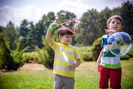 Boy blowing soap bubbles while an excited kid enjoys the bubbles. Happy teenage boy and his brother in a park enjoying making soap bubbles. Happy childhood friendship concept. Banco de Imagens