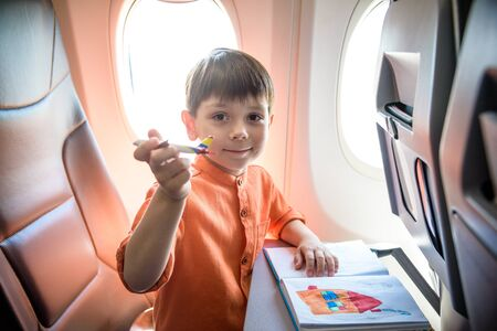Charming kid traveling by an airplane. Joyful little boy sitting by aircraft window during the flight. Air travel with little kids.