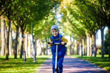 One handsome boy riding a scooter in an autumn park. Standard-Bild - 131996636