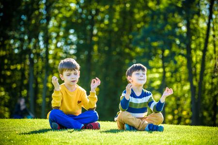 Two Caucasian boy brother friends sitting on fresh green grass field and make meditation dressed in casual clothes, happy kids enjoying peaceful summer weekend outdoors. Friendship relaxation concept. 版權商用圖片 - 131997389