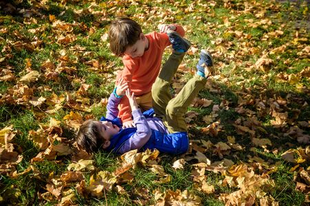 Two boys fighting outdoors. Friends wrestling in summer park. Siblings rivalry. Aggressive kid hold younger boy on ground, try to hit him.