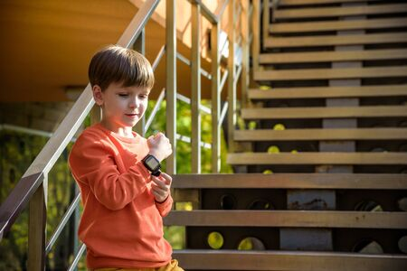 Photo of the boy looking at a smart watch. Children and modern technology. Kid calling to his friends or parents after school. Stock Photo