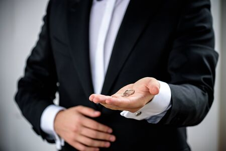 Two wedding rings on groom s hand during ceremony. Groom wear black festive expensive suite. Make proposition to bride.