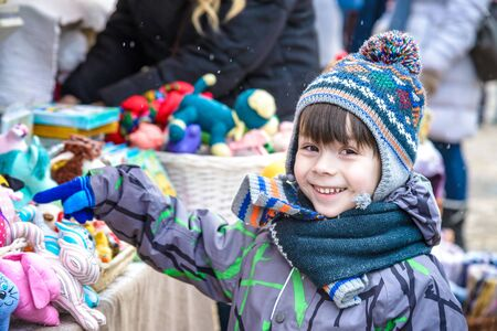 Little cute kid boy selecting decoration on Christmas market. Beautiful child shopping for toys and decorative ornaments. Traditional winter holiday event.