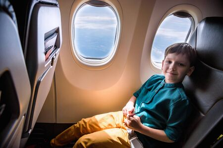 cute little boy traveling by an airplane. Child sitting by aircraft window and playing with toy plane. Traveling abroad with kids.