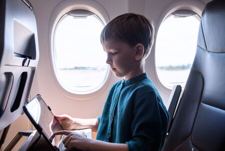 Cute six years old boy, playing on tablen in aircraft on boar, traveling on vacation with parents and siblings. Reklamní fotografie
