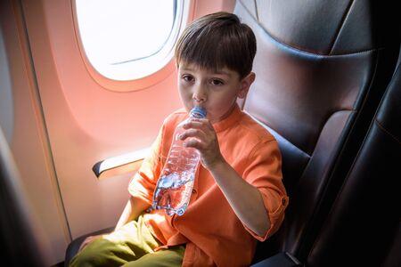 Charmantes Kind, das mit einem Flugzeug reist. Trinkwasser des kleinen Jungen während des Fluges. Flugreisen mit kleinen Kindern.