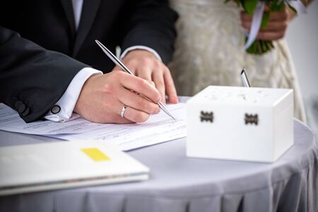 Man signing a marriage register as a groom or witness with a stylish fountain pen with two wedding rings and red flowers, symbolic of love. Foto de archivo