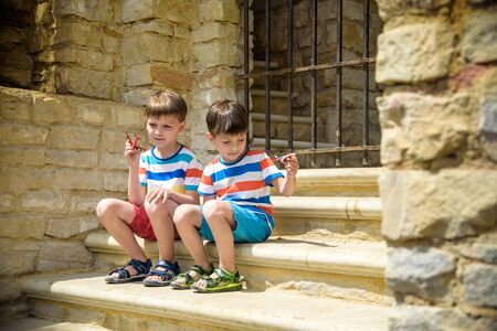 The children playing on the ruins of ancient building with metal gate an archaeological site of an ancient city. Two boys sitting and play with toy aircraft plane. Travel concept. 版權商用圖片 - 142894859