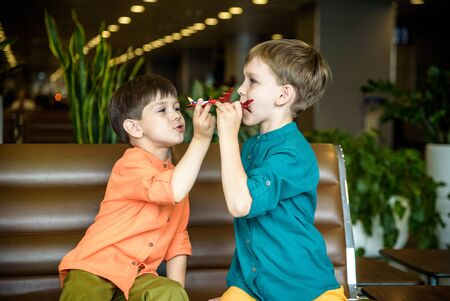 Two young brother boy dreaming of becoming a pilot. A child with a toy airplane plays at airport waiting for departure on their aircraft. Travel and holidays with children concept. 免版税图像