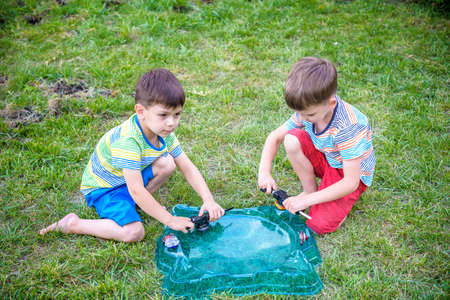 Two Boys playing with modern spin top outdoors. Entertainment game for children. Top, triggered by a trigger. Kids having a tournament on arena or battle field. Top view.