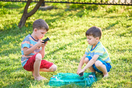 Two Boys playing with modern spin top outdoors. Entertainment game for children. Top, triggered by a trigger. Kids having a tournament on arena or battle field. 写真素材