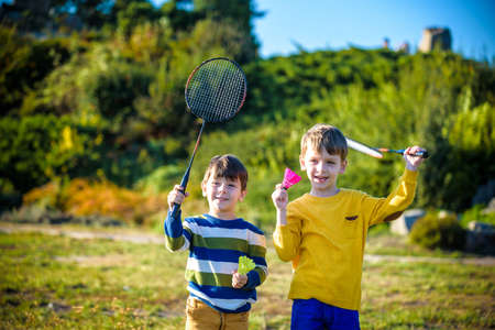 Two active preschool boy playing badminton in outdoor court in summer. Kids play tennis. School sports for children. Racquet and shuttlecock sport for child athlete. Friends happy together warm field.