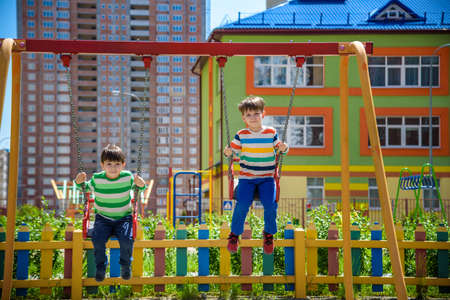 Two little kid boys having fun with swing on outdoor playground. Children, best friends and siblings swinging on warm sunny spring or autumn day. Active leisure with kids. Casual boy fashion.