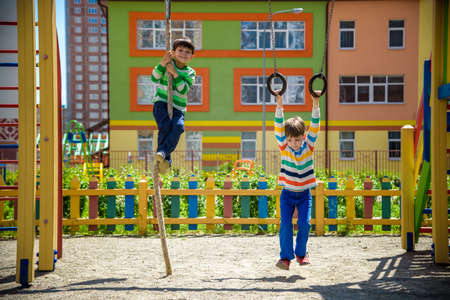 Two brothers sibling boy in casual clothes on playground climbing rope and athletic rings. Kids has a lot of fun. Healthy leisure time with children. Family competition friendship concept.