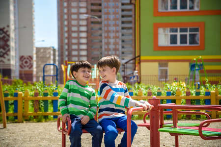 two cheerful boys in t-shirts play on a big iron carousel on the playground at the summer or spring warm day in kindergarten. Kids has a lot of fun. Friendship concept.