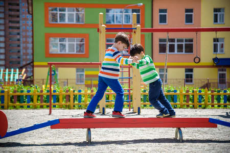 Two little school and preschool kids boys playing on playground outdoors together. children having competition standing on log with outdoor activities in summer sunny day.