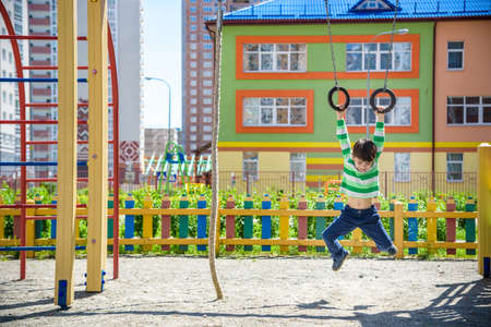 Cute little kid boy enjoying climbing athletic rings on a playground. Toddler child learning to climb, having fun on warm sunny spring day. Active leisure with kids 写真素材