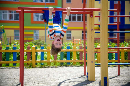Happy child boy hanging upside down on bar, playground in city, outdoor activities