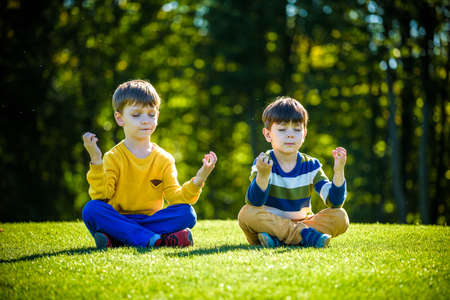 Two Caucasian boy brother friends sitting on fresh green grass field and make meditation dressed in casual clothes, happy kids enjoying peaceful summer weekend outdoors. Friendship relaxation concept.