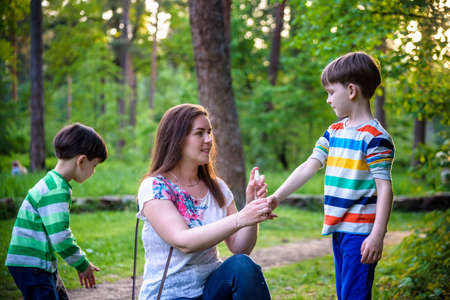 Young woman mother applying insect repellent to her two son before forest hike beautiful summer day or evening. Protecting children from biting insects at summer. Active leisure with kids. 写真素材